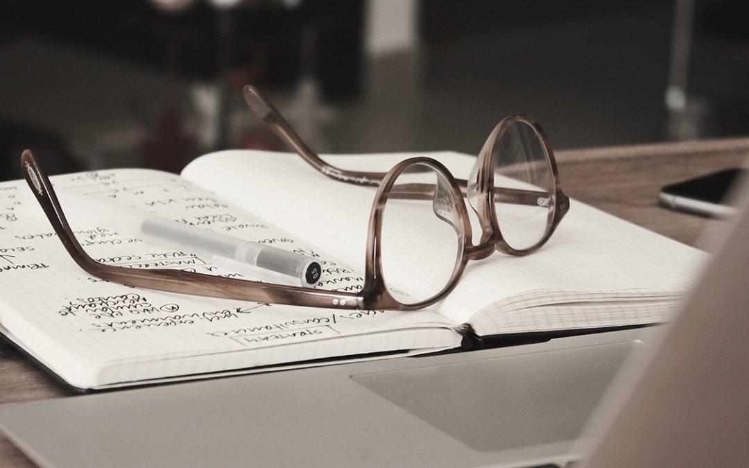 Close up of glasses resting on a notebook in front of laptop