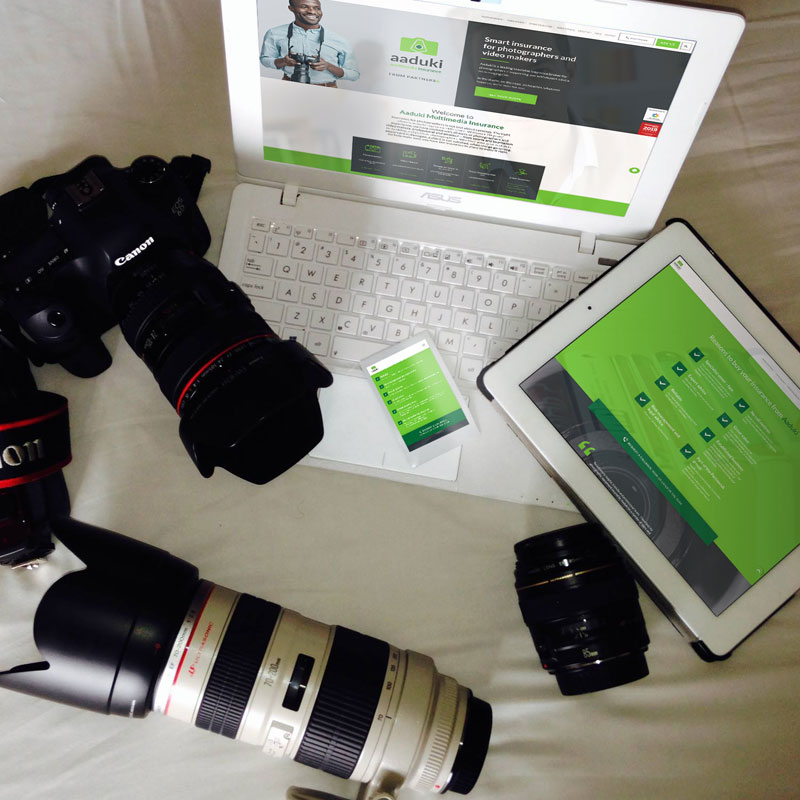 Pic showing various digital devices all displaying the Aaduki website next to a camera and lenses